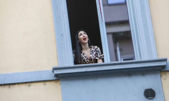 A girl sings from the window during the flash mob, March 13, 2020. Some people have organized a flash mob asking to stand on the balcony and sing or play something, to make people feel united in the quarantine. Mairo Cinquetti/NurPhoto via Getty Image